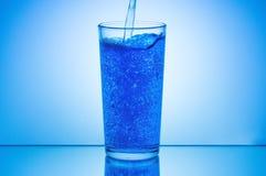 Acqua di versamento in vetro su fondo blu Fotografia Stock Libera da Diritti