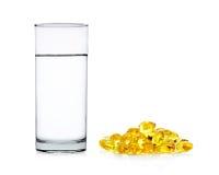 Acqua di vetro con le capsule dell'olio di pesce isolate sulla parte posteriore di bianco immagine stock libera da diritti
