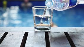 Acqua dolce di versamento in un vetro che sta sulla tavola di legno vicino alla piscina Movimento lento HD, 1920x1080 archivi video