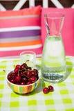 Acqua e ciliege del Carafe immagine stock libera da diritti