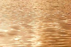 Acqua e tramonto dell'oro per gli ambiti di provenienza Fotografia Stock