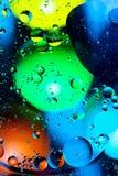 Acqua ed olio mescolantesi sui cerchi e sugli ovali astratti delle palle di bello colore di una pendenza del fondo immagini stock libere da diritti