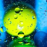 Acqua ed olio mescolantesi sui cerchi e sugli ovali astratti delle palle di bello colore di una pendenza del fondo fotografia stock libera da diritti