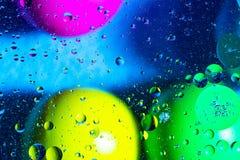Acqua ed olio mescolantesi sui cerchi e sugli ovali astratti delle palle di bello colore di una pendenza del fondo fotografie stock