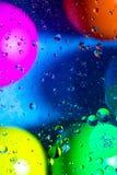 Acqua ed olio mescolantesi sui cerchi e sugli ovali astratti delle palle di bello colore di una pendenza del fondo immagini stock