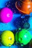 Acqua ed olio mescolantesi sui cerchi e sugli ovali astratti delle palle di bello colore di una pendenza del fondo fotografia stock