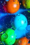Acqua ed olio mescolantesi sui cerchi e sugli ovali astratti delle palle di bello colore di una pendenza del fondo fotografie stock libere da diritti