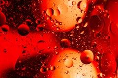 Acqua ed olio mescolantesi sui cerchi e sugli ovali astratti delle palle di bello colore di una pendenza del fondo immagine stock libera da diritti