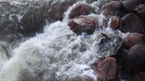Acqua a flusso rapido in un'insenatura che precipita sopra i massi stock footage