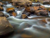 Acqua fredda che corre fra le rocce fotografia stock