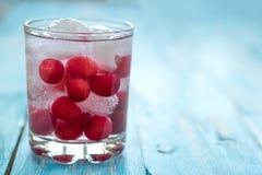Acqua fredda con ghiaccio, le ciliege e le bacche Immagine Stock Libera da Diritti