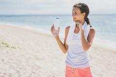 Acqua minerale bevente della donna sportiva dopo l'allenamento per i refreshmen Fotografia Stock