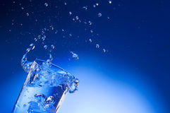 Acqua minerale che spruzza fuori dal vetro Immagini Stock