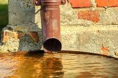 Acqua piovana che scorre dal primo piano del tubo di scarico Fotografia Stock