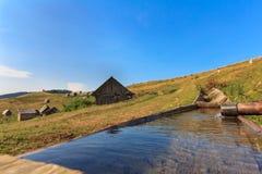 Acqua potabile da una depressione di legno Fotografie Stock