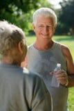 Acqua potabile degli anziani dopo forma fisica in sosta immagini stock