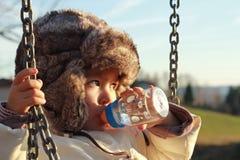 Acqua potabile del bambino dall'alimentatore Immagini Stock