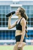 Acqua potabile del bello atleta della ragazza Immagini Stock