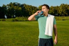 Acqua potabile del bello sportivo sul prato inglese Fotografia Stock