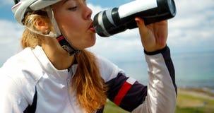 Acqua potabile del ciclista femminile su una strada 4k della campagna stock footage