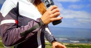 Acqua potabile del ciclista femminile su una strada 4k della campagna video d archivio