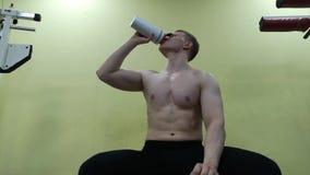 Acqua potabile del giovane nella palestra Il tipo usa una scossa della proteina