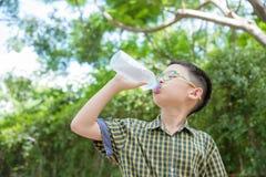 Acqua potabile del ragazzo dalla bottiglia Fotografia Stock
