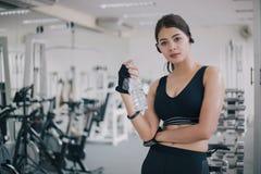 Acqua potabile dell'Asia della donna sportiva dopo gli esercizi nella palestra Forma fisica - concetto di sano fotografie stock libere da diritti