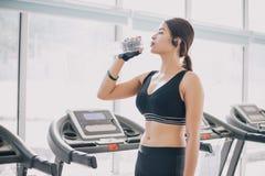 Acqua potabile dell'Asia della donna sportiva dopo gli esercizi nella palestra Forma fisica - concetto di sano fotografia stock