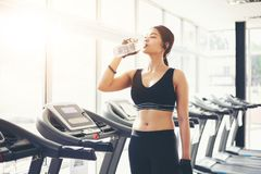 Acqua potabile dell'Asia della donna sportiva dopo gli esercizi nella palestra misura fotografia stock