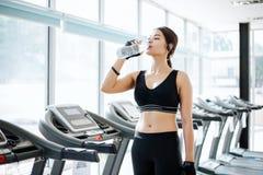 Acqua potabile dell'Asia della donna sportiva dopo gli esercizi nella palestra misura fotografia stock libera da diritti