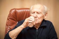 Acqua potabile dell'uomo anziano Fotografia Stock