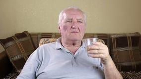 Acqua potabile dell'uomo anziano da un vetro archivi video