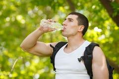 Acqua potabile dell'uomo attivo da una bottiglia, all'aperto Il giovane maschio muscolare estigue la sete Fotografie Stock Libere da Diritti