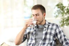 Acqua potabile dell'uomo a casa fotografia stock