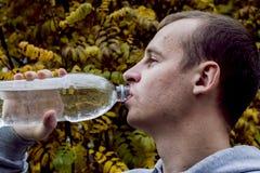 Acqua potabile dell'uomo da una bottiglia fuori fotografia stock