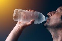Acqua potabile dell'uomo dalla bottiglia Immagini Stock Libere da Diritti