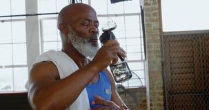 Acqua potabile dell'uomo senior nello studio 4k di forma fisica video d archivio