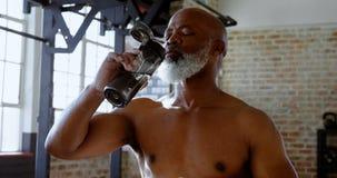 Acqua potabile dell'uomo senior nello studio 4k di forma fisica archivi video