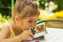 acqua potabile della bambina sveglia dalla tazza nel giorno di estate Immagine Stock