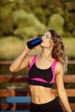 Acqua potabile della bella di forma fisica donna dell'atleta dopo l'allenamento che si esercita sull'estate di sera di tramonto a Immagini Stock Libere da Diritti