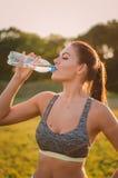 Acqua potabile della bella donna di forma fisica e sudare dopo il exerci fotografie stock libere da diritti