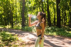 Acqua potabile della bella donna di forma fisica e sudare dopo l'esercitazione il giorno caldo di estate in parco Atleta femminil immagini stock libere da diritti