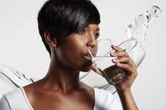Acqua potabile della donna abbastanza africana Fotografia Stock