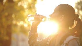 Acqua potabile della donna contro i raggi di sole stock footage