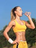 Acqua potabile della donna dell'atleta fotografie stock