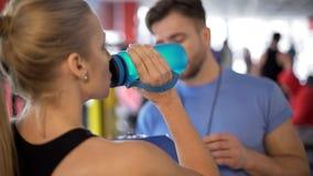Acqua potabile della donna dell'atleta ed ascoltare il consiglio della vettura dopo l'allenamento in palestra fotografia stock