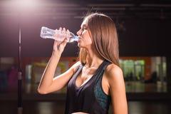 Acqua potabile della donna di forma fisica dalla bottiglia Giovane femmina muscolare alla palestra che prende una rottura dall'al Fotografie Stock