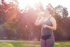 Acqua potabile della donna di peso eccessivo dopo l'allenamento Immagini Stock