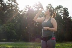 Acqua potabile della donna di peso eccessivo dopo l'allenamento Fotografia Stock Libera da Diritti